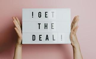 Two hands holding a sign that says get the deal over a pastel pink background, styling and design concept, copy space, buy online and e-commerce photo