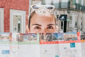 Close up of a young woman looking straight to camera while covering his face with a map, tourism and travel concepts photo