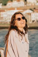 Young woman using sunglasses smiling a lot while touching them, sunglasses concept, summer and travel,copy space photo