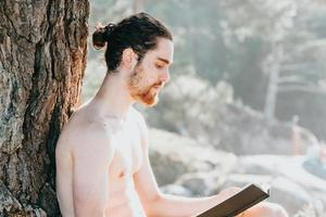 Close up of a man with a beard reading a book shirtless next to a tree during summertime photo