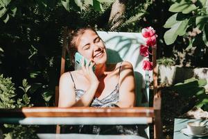 Mujer riendo mientras realiza una llamada telefónica en un jardín soleado durante las vacaciones, relajarse trabajando desde casa foto