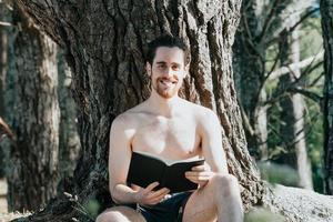 A young hippie man in trunks shirtless reading a book and smiling to camera against a tree during a summer day, relax and chill concepts, good life, young people photo