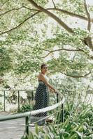 Woman in a forest near a handrail with a dress looking to camera, liberty freedom anxiety concept, self care, forest ambient photo