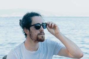 Young man using sunglasses smiling a lot while touching them, sunglasses concept, summer and travel,copy space photo