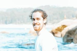 Young hipster male with long curly hair and beard smiling to camera during a sunny day at the beach, happiness and relax concepts photo