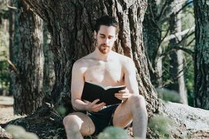 A man in trunks shirtless reading a book against a tree during a summer day, relax and chill concepts, good life, young people photo