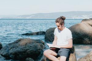 Varón joven con cabello largo leyendo un libro en la orilla de la playa durante un día brillante, copie el espacio, el concepto de relajación y meditación foto