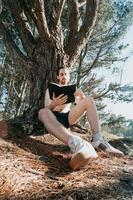 Young hippie male reading a book, wide angle shot, social network, summer vibes relaxed lifestyle photo