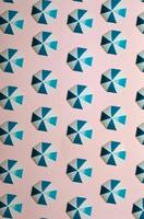 Pattern of blue umbrellas over a pastel pink background, minimalism, design and digital resource, background with copy space photo