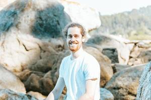 Young man smiling to camera during a sunny day, happiness concept, beach and holiday, reflection and yoga concepts photo