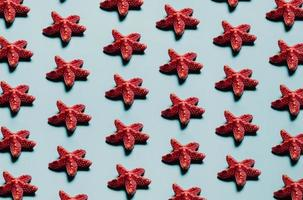 Pattern of starfish over a pastel blue background, minimalism, design and digital resource, background with copy space photo
