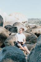 Young man looking away from camera while reading a book on the shore of the sea, copy space, confidence and study concepts, future and self help photo