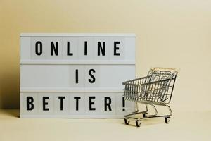 Online is better sign, commercial shot, e-commerce concept, shop cart with a pastel yellow background, copy space and minimal styling photo