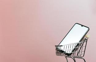 carrito de compras con un teléfono móvil en blanco sobre un fondo rosa pastel, comercio electrónico, compra en línea, comercio en línea, fondo, tecnología, día de compras, viernes negro y red, espacio de copia, maqueta foto