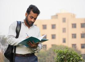young Male collage Student Standing outside at campus and reading Book photo