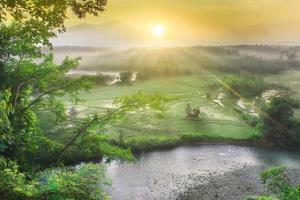 vista de la mañana en hermosos campos de arroz y montañas brumosas foto