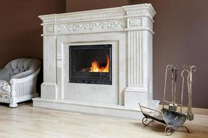 White marble fireplace in classic style with burning wood inside. photo