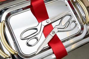 Tijeras de metal plateado utilizadas para ceremonias de apertura con un corte de cinta roja en una bandeja de metal foto