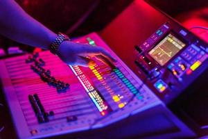 Sound engineer working with concert sound equiplment- audio mixing music console with backlit buttons. photo