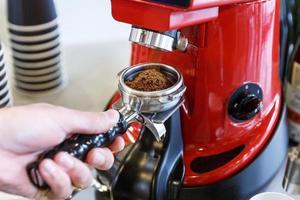 camarero en un café moliendo granos de café frescos en una máquina de molienda de café. foto