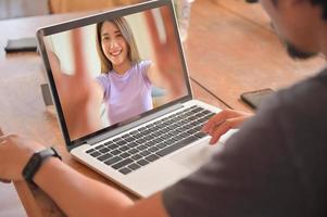 los hombres jóvenes que usan la computadora portátil están charlando en línea con amigas. foto
