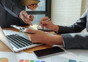 El equipo de administración trabaja en una tableta para resumir el trabajo para lograr los objetivos de la organización. foto