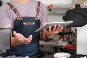 barista holding a tablet in hand, recommending menu and receiving orders from customers. photo