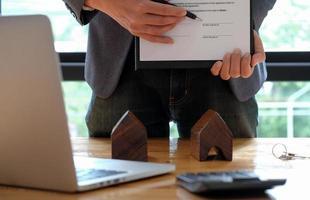 empresarios vendiendo la casa apuntando a la firma del contrato de compraventa en la oficina. foto