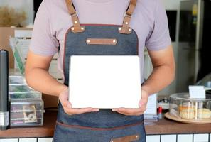 Barista hold blank screen tablet to receive menu from customer in the cafe. photo