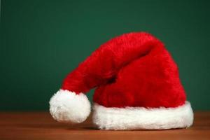 Gorro de Papá Noel rojo con espacio de copia sobre fondo verde y madera foto