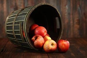 Barril lleno de manzanas rojas sobre fondo de madera grunge foto