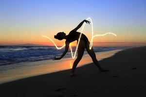 Joven bailarina experta en la playa durante la puesta de sol foto