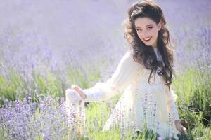Bastante joven al aire libre en un campo de flores de lavanda foto