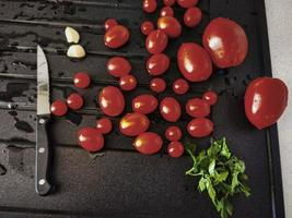 cherry tomatoes, garlic and parsley in Italian cuisine ready to be tasted and eaten photo