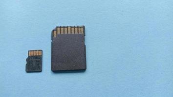 Foto de la tarjeta de memoria grande y pequeña en negro sobre un fondo fotográfico azul