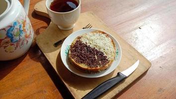 una mini foto de un martabak con cobertura de chocolate y queso rallado encontrado una taza caliente, un cuchillo, un tenedor y cubiertos