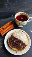 una mini foto de un martabak con cobertura de chocolate y queso rallado, se encontró una taza caliente, un cuchillo, un tenedor y cubiertos