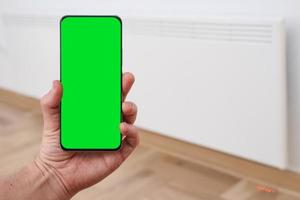 Smart heater convector control by phone app. Smart Home with the smart heating system. Electric panel heating concept. Chroma key, green screen. photo