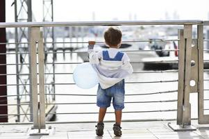 Small boy watching curiously yachts from behind the fence with ballun photo