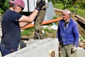 Un trabajador de hormigón en un sitio de construcción hormigona las paredes con una máquina foto