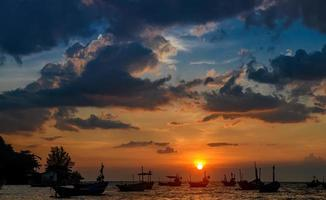 Silhouette fishery boats in the sunset time. photo