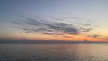 Seascape with sunset and boat on the horizon video