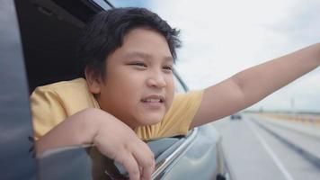 chico lindo asiático estaba sentado junto a la ventana y disfrutando de la vista en el camino. video