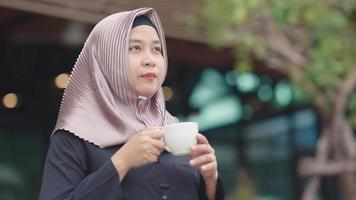 Muslim Asian working women drinking coffee in the morning with a happy face video