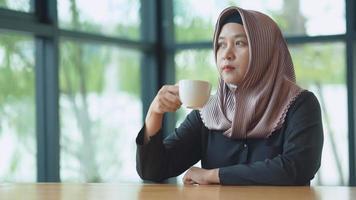 Mujeres trabajadoras asiáticas musulmanas bebiendo café por la mañana con una cara feliz video