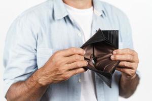 Hombre maduro molesto sosteniendo su billetera vacía sobre fondo blanco. crisis financiera, quiebra, sin dinero, concepto de mala economía. foto