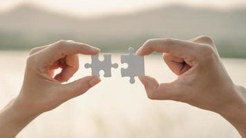 mano de mujer y hombre conectando una pieza de rompecabezas en el fondo de la montaña y el lago. símbolo del concepto de asociación y conexión. estrategia de negocios. foto