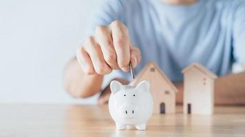 Man hand put coin into White piggy bank with wooden house on wood table. saving money for buying house, financial plan home loan concept. photo