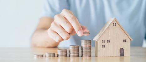 Man hand put coin on coins stack with wooden house on wood table. saving money for buying house, financial plan home loan concept. photo