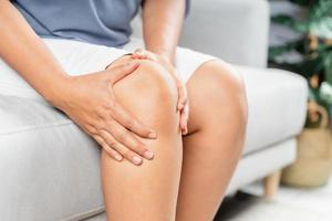 Close up of chubby woman sitting on the sofa and feeling knee pain and she massages her knee. photo